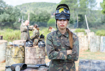 Female paintball player in camouflage and black mask with traces of paint