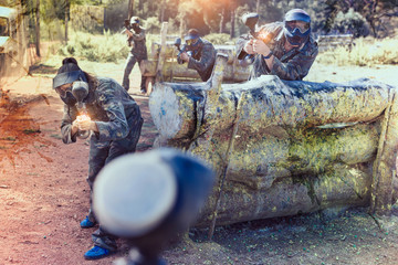 Paintball players aiming and shooting with guns