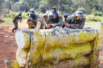 Portrait of team of adult people playing on paintball battlefield outdoor