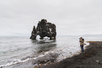 Photographer taking picture of the Rhino rock, Vatnsnes peninsula, Iceland