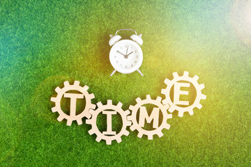 Time, wooden gears, alarm clock on the background of green artificial grass. working time.