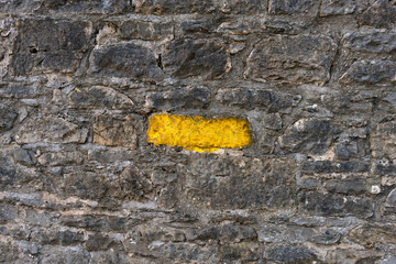 Old gray stone wall with one stone highlighted painted bright yellow