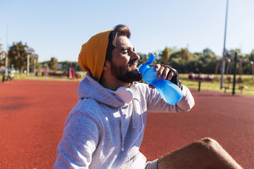 Fit man take a rest and drinking water after training