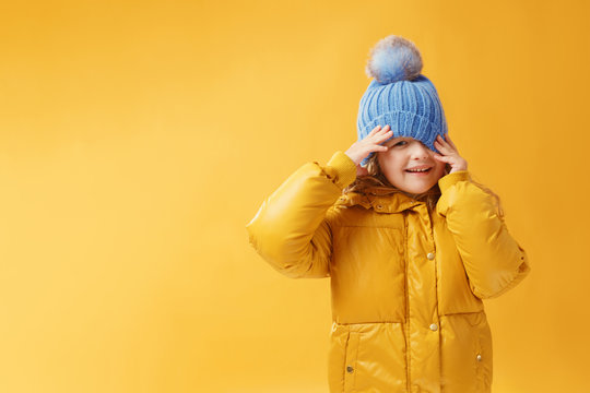 Portrait happy little girl preschooler in a winter jacket and blue hat. Yellow on a yellow background.