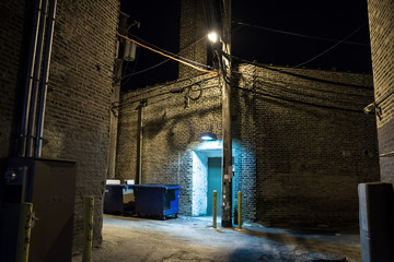 Wall Mural - Dark and scary downtown urban city street corner alley with an eerie vintage industrial warehouse factory entrance and dirty dumpsters at night