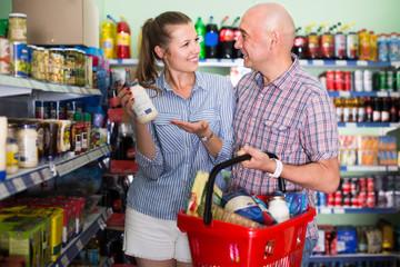 happy woman and man choosing mayonnaise at the modern supermarket