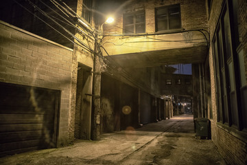 Wall Mural - Dark and scary downtown urban city street alley scene with an eerie vintage industrial warehouse factory skyway at night