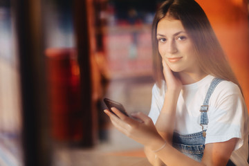 young attractive pretty girl at cafe with coffee and phone throuth window glass