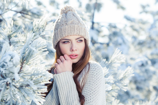 Beautiful winter portrait of young woman in the snowy scenery