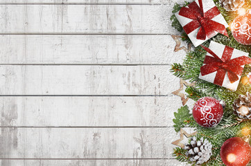 Christmas wooden background with fir branches and ornaments covered with snow