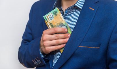 Male hand hiding australian dollar banknotes into pocket