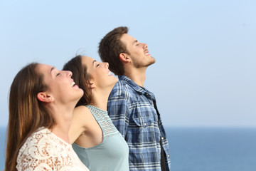 Profile of three friends breathing fresh air on the beach