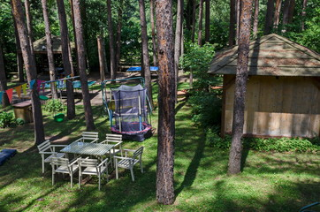 Summer child public bivouac  with table, chair, house and  jumping trampoline in the coniferous forest, near to Pasarel village, Bulgaria