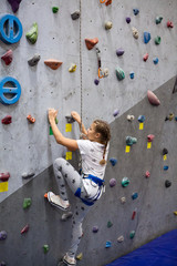 Teenage Caucasian girl climbing wall with holding safety rope, indoor