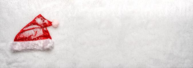 Un chapeau de père noël rouge sur de la neige en format panoramique