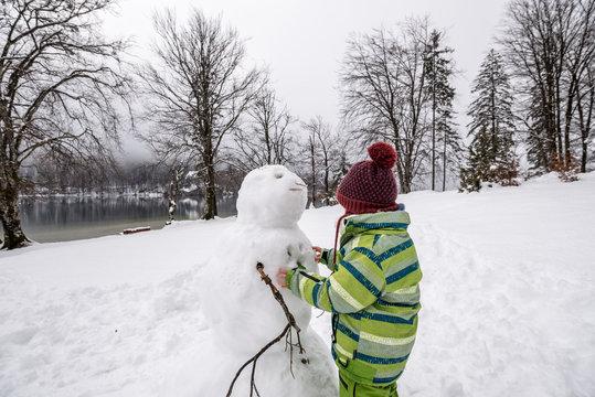 Little boy or girl making a snowman