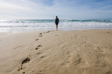 Woman Walking on The Beach. Footprints in Sand.