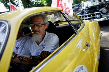 Camyl Bullaudi smokes a cigar in his Karmann Ghia 56 before the beginning of a classic cars rally in Havana