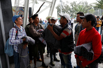 Migrants from Honduras, part of the caravan traveling from Central America en route to the United States, are pictured with blankets delivered after arriving at a sport centre used as a shelter, in Mexico City