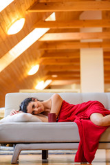A beautiful nude woman wrapped in a cozy blanket relaxing on the