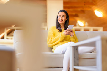 Portrait of a beautiful woman using her smartphone in the living