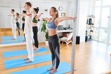 Serious concentrated young people with closed eyes standing up straight on exercise mats and outstretching arms in yoga studio