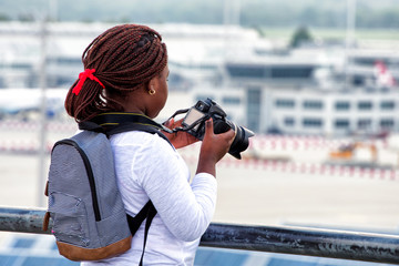 Afro-american girl taking pictures with digital camera on background of airport.