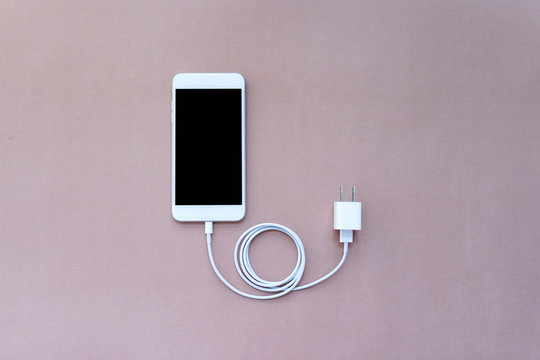 Smartphone Connected with Charger Adapter and USB Cable on Brown Background Top View