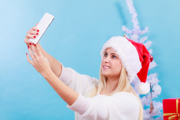 Girl in santa hat taking picture of herself using phone