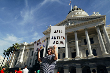 """Amber Cummings holds up signs outside the California State Capitol building during a """"Turn California Red"""" rally that drew a small crowd of anti-fascist counter-protesters in Sacramento"""