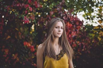Girl in a yellow silk top in an atumn park.