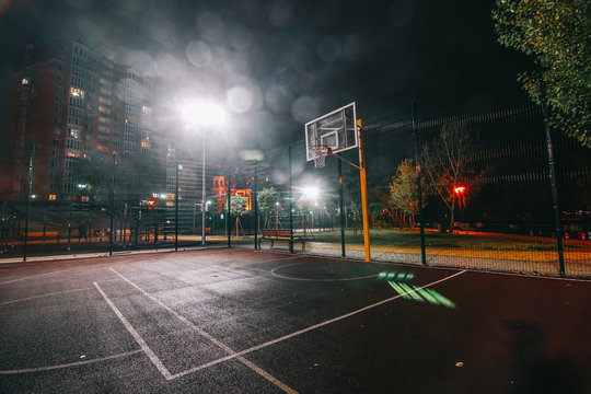 Illuminated basketball playground with red pavement, modern new basketball net and lens flares on background.