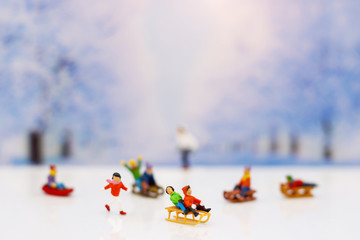 Miniature people: Childrens playing fun with snow slider.