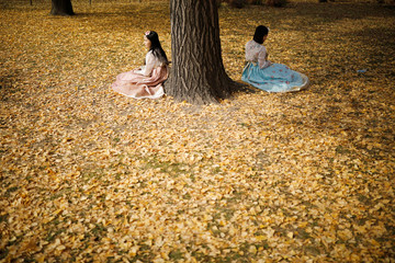 Women wearing the Korean traditional costume Hanbok pose for photographs on an autumn day at Gyeongbok Palace in central Seoul