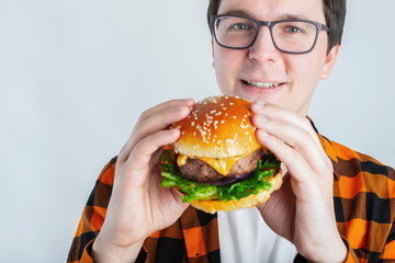 A young guy with glasses holding a fresh Burger. A very hungry student eats fast food. Hot helpful food. The concept of gluttony and unhealthy diet. With copy space for text