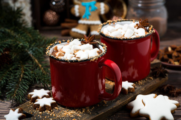 cozy winter drink hot chocolate in red mugs on wooden table