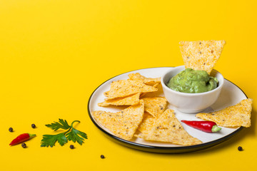 Mexican food Guacamole dip With Corn Chips on yellow background