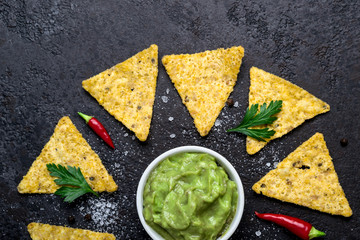 Black food background with guacamole and corn chips