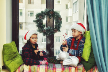 Funny kids waiting for Christmas . Brother and sister on the window dressed in Santa hats