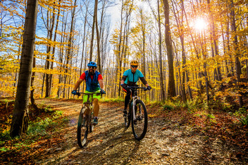 Wall Mural - Cycling woman and man at Beskidy mountains autumn forest landscape. Couple riding MTB enduro track. Outdoor sport activity.