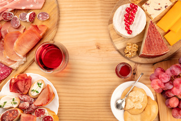 Charcuterie Tasting. A photo of many different sausages and hams, lunch meats, and a cheese platter, shot from above on a rustic background with a glass of red wine and copy space
