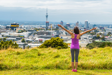 Auckland city skyline view from Mount Eden of Sky tower, New Zealand. Happy woman with arms up in freedom and happiness at top of Mt Eden urban park famous tourist attraction.
