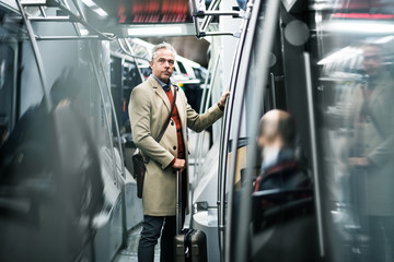 Mature businessman with suitcase travelling by subway in city.