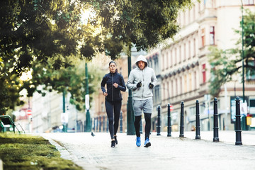 A fit couple running outdoors on the streets of Prague city.