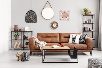 Leather sofa with pillows and blanket in the middle of elegant living room interior with metal shelves and modern coffee table, real photo
