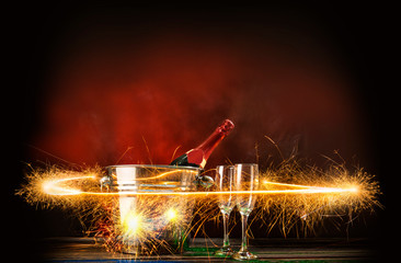 Champagne bottle in ice bucket with two of glasses and fireworks display