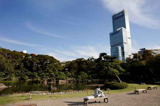 A man reads a book on a bench in a park in Osaka