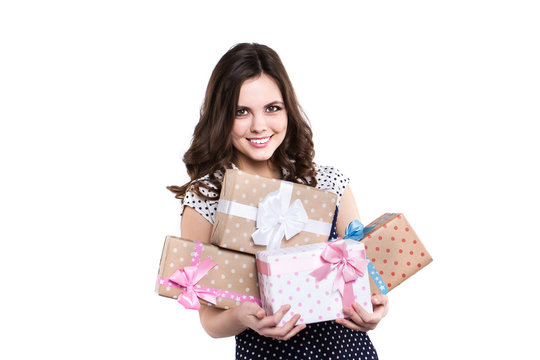 Happy smiling woman holding gift boxes.