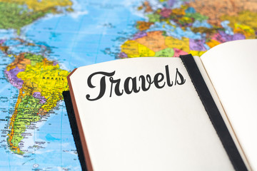 A retro notepad with text travels with world map and toy suitcase
