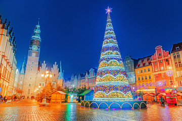 Illuminated Christmas tree at central Square of old city on Christmas Market in Wroclaw, Poland. New Year ambiance, illuminated and ornamented festive city. Night scene. European traditions.